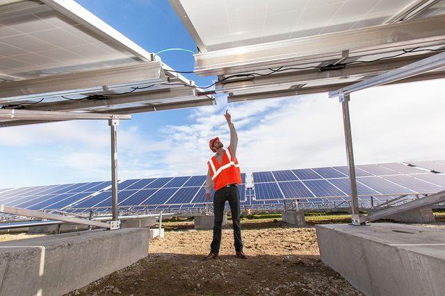 Solar photovoltaic installer examining racking for a PV array